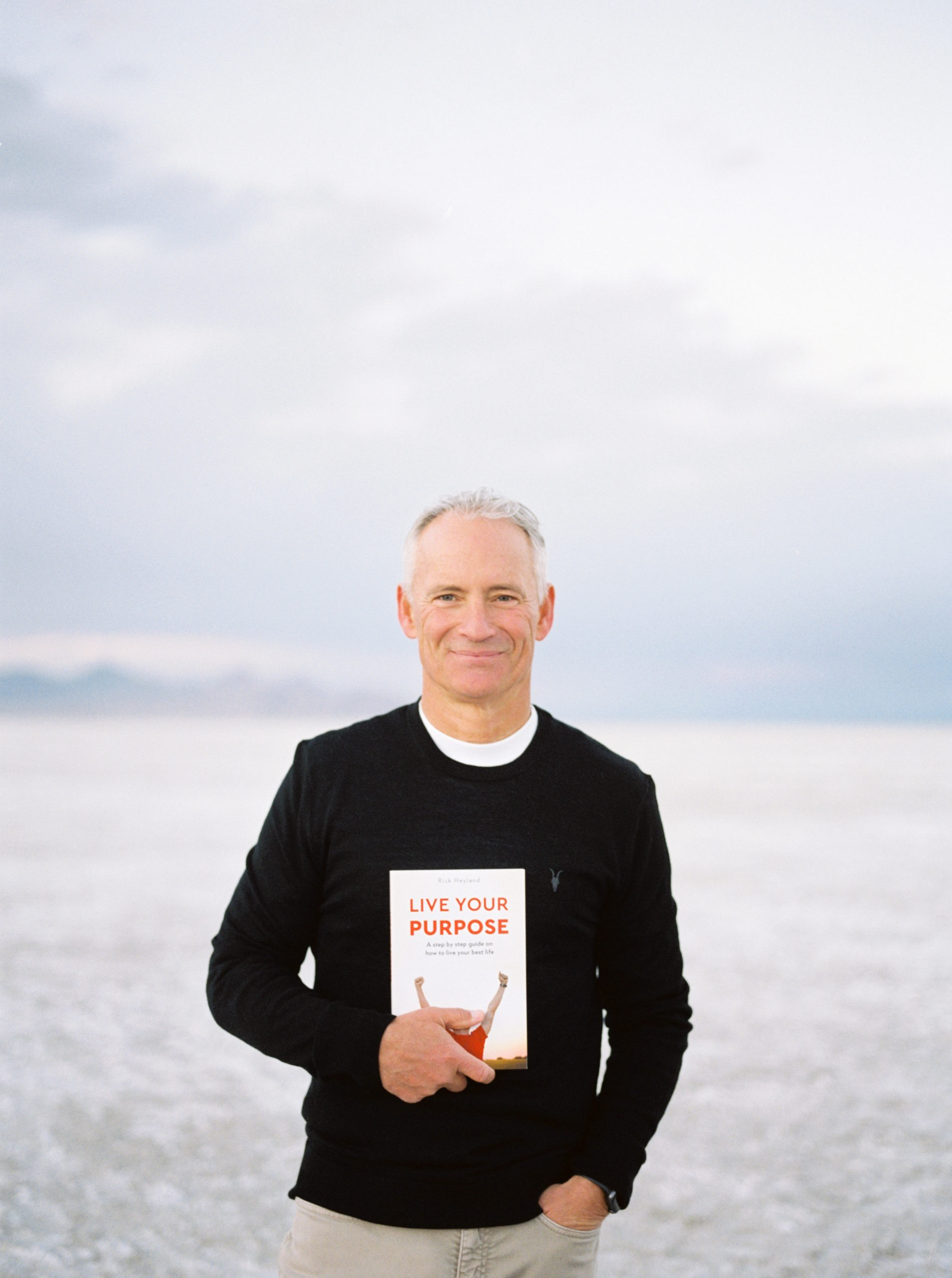 Rick Heyland at the beach holding a copy of Live Your Purpose
